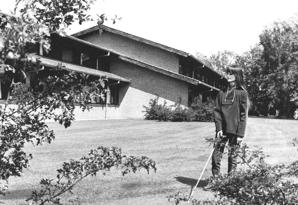 Foto i sort/hvis af kvinde fra 60'erne med mobilitystok foran IBOS