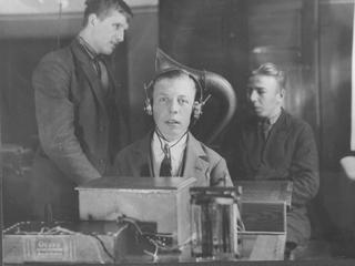 Historisk billede fra IBOS: Sort-hvid-billede af dreng med høretelefoner på.