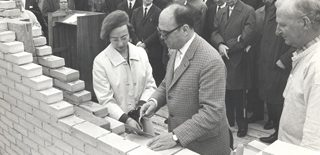 Historisk billede fra IBOS: Sort-hvid billede af mand og kvinde ser på modelbygninger af IBOS