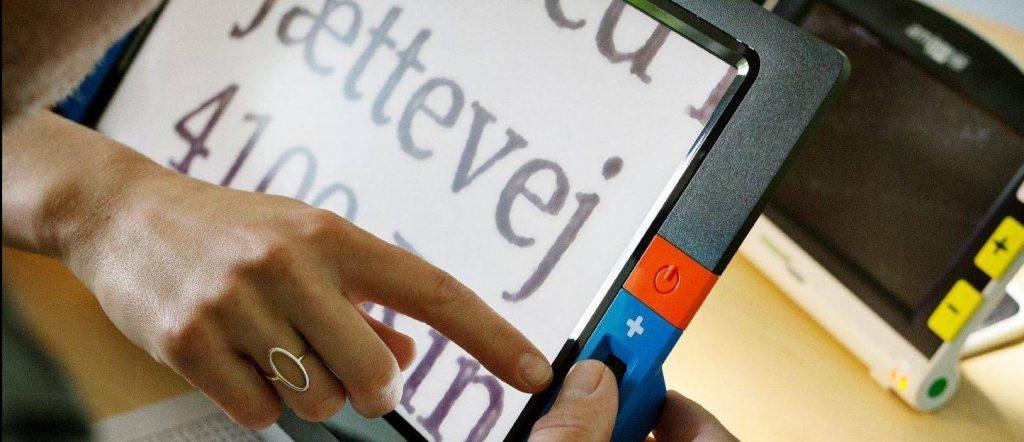 Mand sidder med iPad med forstørret tekst. En kvindes hånd peger på skærmen.