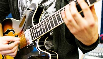 Nærbillede af en elev, der spiller guitar.