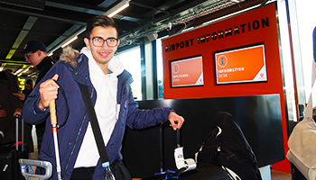STU elev i lufthavnen, står med sin mobilitystok, foran informationsskærm