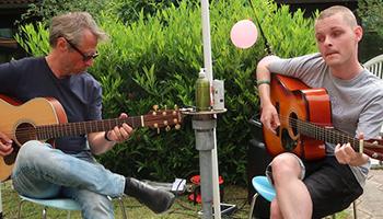 Elev og lærer spiller guitar i IBOS gårdhave