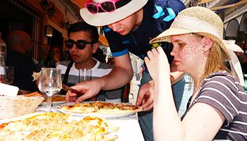 3 elever spiser pizza i solen på studietur