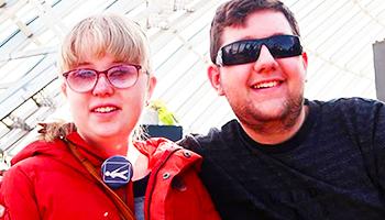 To smilende STU-elever, med sorte briller og svagsynsbadge.