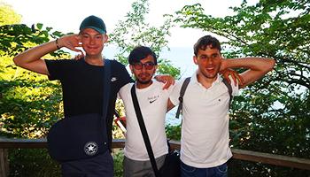 3 smilende drenge foran udsigt over træer og havet på studietur