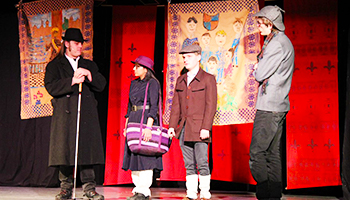 Foto fra teaterforestilling, hvor 4 personer er på scenen i kostumer.